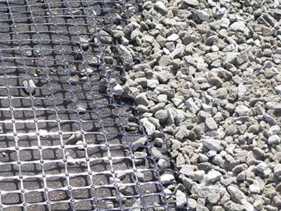 A piece of biaxial geogrid on the base and several gravels on it.