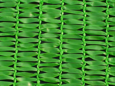 A piece of green shade cloth with flat strands on the table.