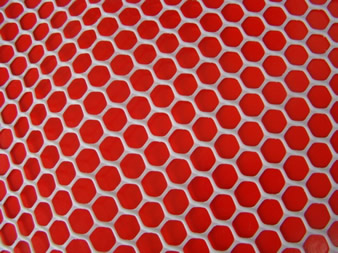 A piece of white hexagonal extruded plastic mesh on the red background.