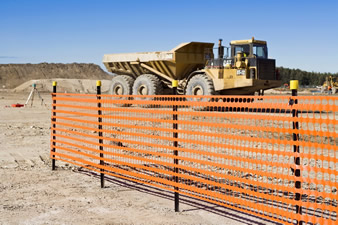 The orange warning barrier fence is fixed on the posts and a machine is working in the construction site.