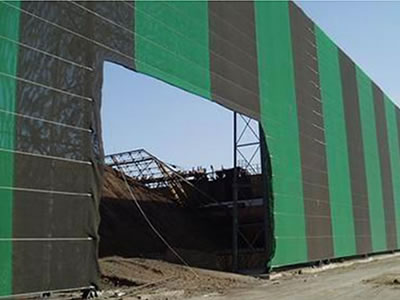 Green and black color flexible windbreak netting is installed surrounding the coal mine yard.