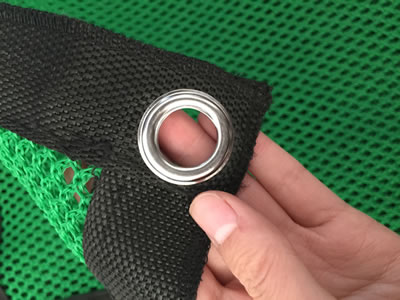 A hand is holding the metal button hole of flexible windbreak netting.