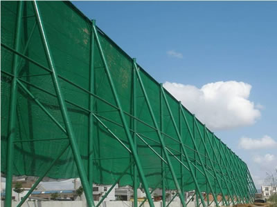 The green color flexible windbreak netting is installed beside of the river bank.