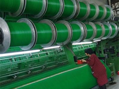 A machine is producing green color flexible windbreak netting and a roll of netting on the ground.