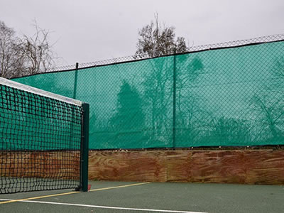 Green color flexible windbreak netting is attached onto the chain link fencing of tennis court.
