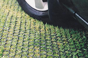A car is parking on the grassland and the grassland is covered by the hexagonal grass protection mesh.