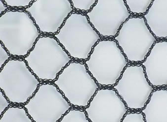 A piece of black hexagonal knitted bird netting on the white background.