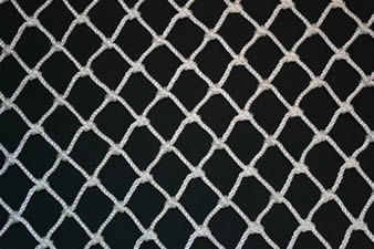 A piece of white diamond knotted plastic mesh on the black background.