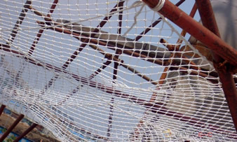 A piece of white knotted plastic mesh is installed on the scaffolds.