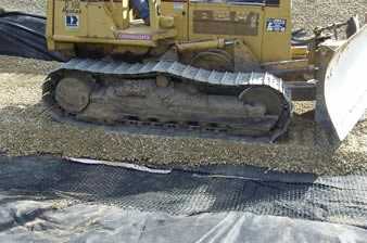 Quaxial plastic geogrid is installed on the geotextile and a bulldozer is paving the gravels.