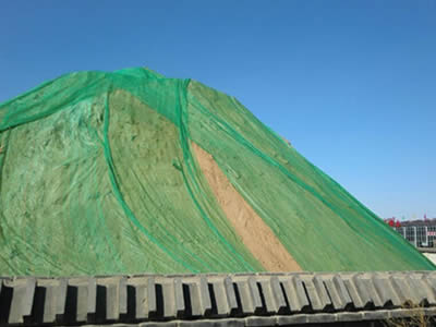 Green shade cloth is covering an soil mountain.